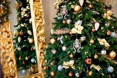 Beautiful decorated Christmas tree with red and goldish baubles and garland, in the new-year background with fireplace stock image