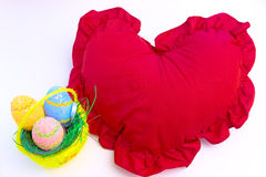 Marking Easter to us and in the world. Beautiful decorated Easter eggs in a yellow basket,next to red heart-shaped pillow, photography Royalty Free Stock Photography