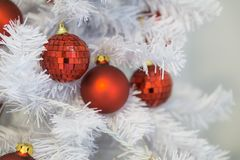 Beautiful decorated white christmas tree with red bulbs and lights royalty free stock photos