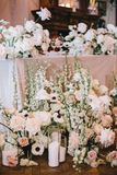 Beautiful decoration of the newlyweds` table, flower arrangement of white and pink roses with buttercups, decorative stock image