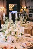 Beautiful decoration of wedding tables with compositions from flowers of white roses and buttercups with decorative stock photo