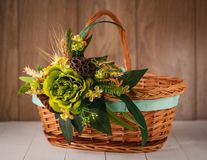 Basket with flowers to celebrate Easter on a wooden background Royalty Free Stock Photos
