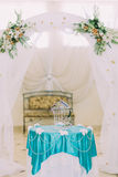 Beautiful decorative birdcage on fancy decorated table under wedding arch  in stylysh vintage interior Royalty Free Stock Image