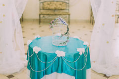 Beautiful decorative birdcage with some cute flowers  in stylysh vintage interior between two curtains Royalty Free Stock Photo