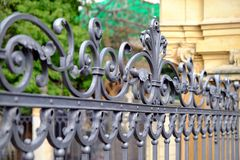 Beautiful decorative cast metal wrought fence with artistic forging. Iron guardrail close up.  Stock Photos