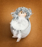 Beautiful decorative doll sitting in the ceramic bowl Royalty Free Stock Photography