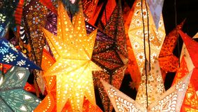 Beautiful decorative paper glowing Christmas stars lights on Christmas market in Germany. Beautiful decorative paper glowing Christmas stars lights on the stock footage