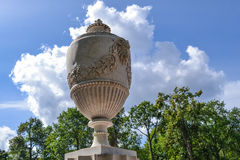 Beautiful decorative vase in the Park of Peterhof. White vase with floral ornaments on the background of trees and clouds. Antique vase, decoration of the Park Stock Image