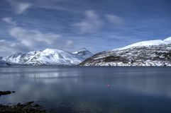 Beautiful deep blue fjord water view with mighty snowy mountain backdrop in the arctic circle wintertime. Northern norway Royalty Free Stock Photos