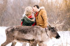 Beautiful deer on the background of a happy family in winter in a snowy forest stock photo