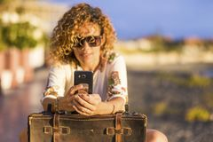 Beautiful defocused curly woman take phone messaging or checking internet for friends. video conference during a travel journey royalty free stock images