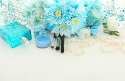 Beautiful and delicate blue flowers arrangement next to pearls necklace, fresh perfume and makeup Royalty Free Stock Photos