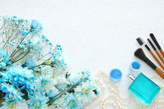 Beautiful and delicate blue flowers arrangement next to pearls necklace, fresh perfume and makeup Stock Photo