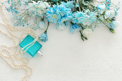beautiful and delicate blue flowers arrangement next to pearls necklace and fresh perfume Stock Photo