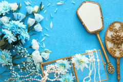 beautiful and delicate blue flowers arrangement next to pearls necklace and hand mirror Stock Photos