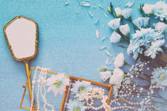 beautiful and delicate blue flowers arrangement next to pearls necklace and hand mirror Stock Photo