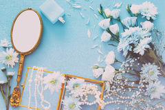 beautiful and delicate blue flowers arrangement next to pearls necklace and hand mirror Stock Photography