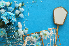 beautiful and delicate blue flowers arrangement next to pearls necklace and hand mirror Royalty Free Stock Image