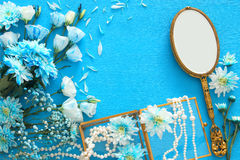 beautiful and delicate blue flowers arrangement next to pearls necklace and hand mirror Royalty Free Stock Photos