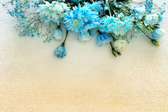 beautiful and delicate blue flowers arrangement on white wooden background stock photography