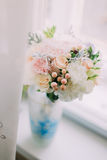 Beautiful delicate bouquet of pink and orange roses in a blue vase on the windowsill,  white interiour Royalty Free Stock Image