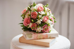 A beautiful delicate bouquet of roses and white irises on the books. Wedding decoration Stock Photos