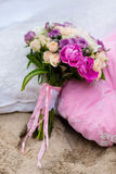 Beautiful, delicate bridal bouquet among decorations with pillow.  Stock Photography