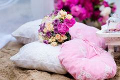 Beautiful, delicate bridal bouquet among decorations with pillow Royalty Free Stock Photos