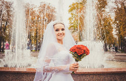Beautiful delicate bride on background of festive fountain Stock Photos