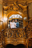 Beautiful delicate bride and handsome elegant groom posing on amazing old stairs with the background of royal wooden Stock Photo