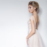 Beautiful delicate bride sexy girl in soft pink skazachno wedding dress with a cut on the chest and back with makeup and evening h Stock Images