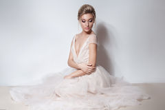 Beautiful delicate bride sexy girl in soft pink skazachno wedding dress with a cut on the chest and back with makeup and evening h Stock Photography