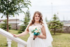 Beautiful delicate bride in white dress in summer royalty free stock images