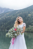 Beautiful delicate girl in the air blue bride wedding dress with luxurious curls in the mountains near the lake with a wedding bou Royalty Free Stock Images