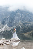Beautiful delicate girl in the air blue bride wedding dress with luxurious curls in the mountains near the lake with a wedding bou Stock Photos