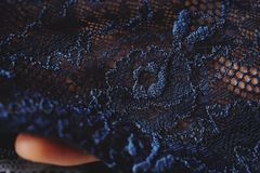 Beautiful delicate openwork dark blue lace in hand Royalty Free Stock Photo