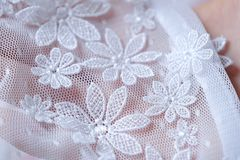 Beautiful delicate openwork white lace in hand Royalty Free Stock Photo