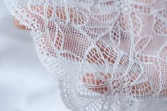 Beautiful delicate openwork white lace in hand Stock Photos