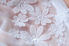 Beautiful delicate openwork white lace in hand Stock Photography