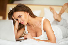 Beautiful delicate smiling young brunette woman laying in bed relaxing using laptop computer. Smiling beautiful woman lying down on bed Royalty Free Stock Images