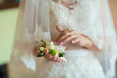Beautiful delicate wedding boutonier with white and pink flowers in the hands of the bride, lace dress and veil, morning of the br. Ide Stock Photography