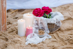 Beautiful, delicate wedding decorations with candles and fresh flowers on the beach Stock Image