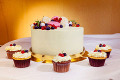 Beautiful delicious fruit pie and cupcakes on the sweet table. Yellow background stock images