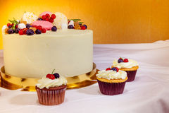 Beautiful delicious fruit pie and cupcakes on the sweet table. Yellow background royalty free stock images