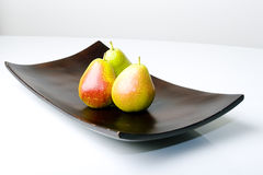 Beautiful delicious pears in a modern style vase. Beautiful delicious fresh pears in a modern style wooden vase Stock Photos