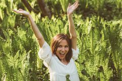Beautiful delight brunette girl hands up in fern. Sunlight royalty free stock images