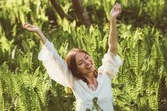 Beautiful delight brunette girl hands up in fern. Sunlight stock photography