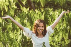 Beautiful delight brunette girl hands up in fern. Sunlight royalty free stock photos