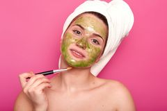 Beautiful delighted female looks directly at camera holding prof brush in one hand, putting light green mask with its help, royalty free stock photography