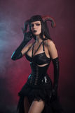 Beautiful demonic girl with horns wearing corset Royalty Free Stock Photo